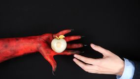 Devil gives a gold paradise apple to a man. 4k stock video