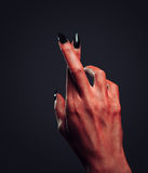 Devil hand with gesture cross fingers Stock Images