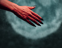 Devil hand with handshake gesture at midnight Stock Photography