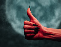 Devil hand with thumb up gesture at midnight Royalty Free Stock Photography