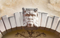 Devil head carved above the stone arch of an Italian villa. Royalty Free Stock Photography