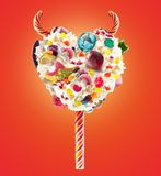 Devil heart Milk shake lolipop with sweets and whipped cream, front view. Sweet devil lolipop concept with whipped cream. And devil horns, devil sweats. Front royalty free stock photo