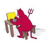 Devil. Man dressed as the devil at a laptop Stock Photo