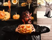 Devil or monster partying. Man wearing scary makeup for Halloween. Devil or monster partying. Man wearing scary makeup with Halloween pumpkins and bats decor on stock photos