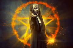 Devil nun woman standing in front of burning pentagram with magi Royalty Free Stock Images