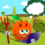 Devil peach holding laptop on a meadow Royalty Free Stock Photo