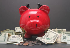 Devil Piggy Bank. A red devil piggy bank with US currency scattered around it Royalty Free Stock Photography