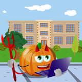 Devil pumpkin holding laptop in front of a school Stock Images
