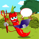 Devil red hot chili pepper holding laptop on a meadow Stock Image