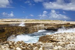 Devil`s Bridge, Antigua. Devils Bridge in the northeast of Antigua where the waves of the Atlantic have eroded a natural arch Royalty Free Stock Images