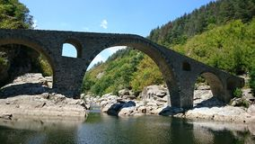 Devil`s Bridge. Is located near Ardino at the foot of the Arda River.According to some, one of the stones shows a footprint of the Devil`s footstep left after stock images