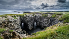 Devil`s eyes - Dungeon National park, Newfoundland. Dungeon national Park, Newfoundland featuring a rare natural occurrence of rock formation under which, two Royalty Free Stock Photo
