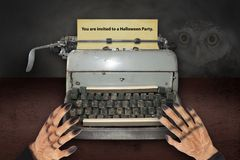 Devil`s hand typing invitations for Halloween with old typewrite. R royalty free stock image