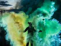 Devil with scary mask surrounded by coloured smoke. Halloween and horror concept stock photos