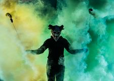 Devil with scary mask surrounded by coloured smoke. Halloween and horror concept stock images