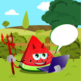 Devil slice of watermelon holding laptop on a meadow Royalty Free Stock Photo