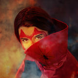 Devil and spider. Haunting reds eyes of a devilish girl looking through smoke, a huge pet spider on the collar of her cape Royalty Free Stock Images