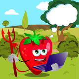 Devil strawberry holding laptop on a meadow Royalty Free Stock Images