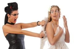 Devil tearing angel wings. Devil women attacking angel, pulling out wings Stock Photo