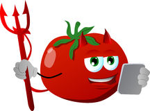 Devil tomato using a tablet Stock Photo