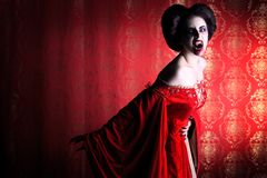 Devil woman. Portrait of a bloodthirsty female vampire over red vintage background Royalty Free Stock Images