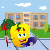 Devil yellow bell pepper holding laptop in front of a school Royalty Free Stock Photo