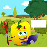 Devil yellow bell pepper holding laptop on a meadow Stock Image