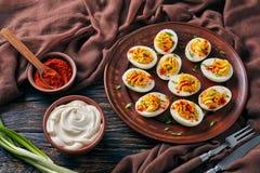 Deviled ägg som strilas med paprika och löken arkivbild