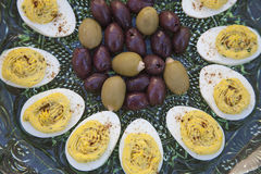 Deviled Eggs and Olives before dinner. Marinated Kalamata olives and green olives stuffed with garlic served with deviled eggs sprinkled with paprika Royalty Free Stock Image