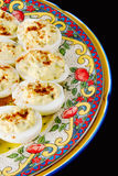 Deviled eggs. Served on a colorful plate that was made in Mexico with no copyright attached with a black background Royalty Free Stock Photos