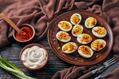 Deviled Eggs sprinkled with paprika and onion. Deviled Eggs sprinkled with paprika and finely chopped green onion on an earthenware plate on an old rustic wooden stock photography