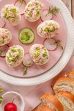 Deviled eggs, stuffed eggs filled with a paste made from smoked ham, mayonnaise, egg yolks and fresh chive on a plate. Deviled eggs, stuffed eggs filled with a stock image