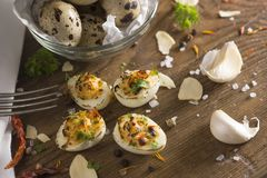 Deviled quail eggs arranged nicely on wooden table with decoration. Deviled quail eggs arranged and decorated nicely on wooden table. Garlic pods, dried garlic Stock Images