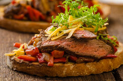 Devilish fried bread. With peppers, chilli and beef steak, topped cheddar cheese and microgreens, with czech beer Stock Photography