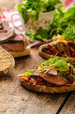 Devilish fried bread. With peppers, chilli and beef steak, topped cheddar cheese and microgreens, with czech beer Royalty Free Stock Photo