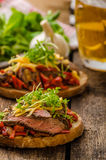 Devilish fried bread. With peppers, chilli and beef steak, topped cheddar cheese and microgreens, with czech beer Royalty Free Stock Images