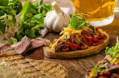 Devilish fried bread. With peppers, chilli and beef steak, topped cheddar cheese and microgreens, with czech beer Royalty Free Stock Photos