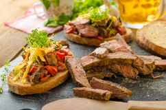 Devilish fried bread. With peppers, chilli and beef steak, topped cheddar cheese and microgreens, with czech beer Stock Photo