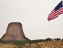 Devils Tower with United States Flag. The two-square-mile park surrounding the tower was proclaimed the nation's first national monument by President royalty free stock photos