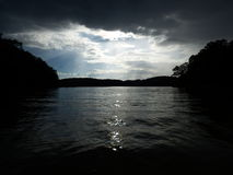 Devine Breach At Redtop Mountain. Beautiful break in clouds with sunlight rays shining down over a dark lake allatoona within the Redtop mountain state park Stock Photo