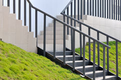 Devious stage with metal handrail. Devious stage with metal hand rail and grass land, shown as composition by shape and line with rhythm, and architecture Royalty Free Stock Photography