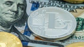 Devise argentée de Litecoin en métal physique au-dessus du billet d'un dollar des Etats-Unis photo libre de droits
