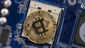 Devise virtuelle de Bitcoin d'or sur de carte mère une unité centrale de traitement à la place nouveau bitcoin de cryptocurrency  banque de vidéos