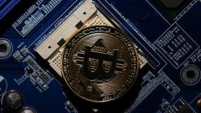 Devise virtuelle de Bitcoin d'or sur de carte mère une unité centrale de traitement à la place nouveau bitcoin de cryptocurrency  clips vidéos