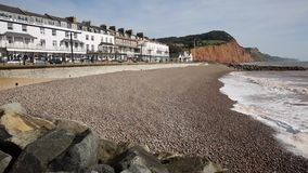Devon coast town of Sidmouth England UK with beach and waves and hotels stock video