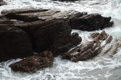 Devon Coast. Water crashing on the rocks along the coast of Devon royalty free stock image