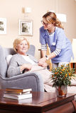 Devoted care and assistance. Portrait of smiling elderly women sitting at home in living room and accepts caregiver assistance Stock Photo