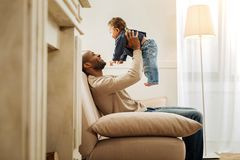 Devoted father spending time with his baby. My pride. Handsome exuberant afro-american daddy laughing and playing with his child while sitting on the sofa Stock Photo