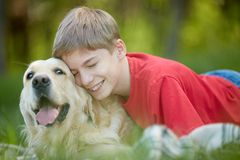 Devoted friends. Portrait of happy lad with his friendly pet lying on green grass Stock Photo