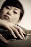 Devoted Guitarist. Asian girl devoted in playing wooden classic guitar stock photography